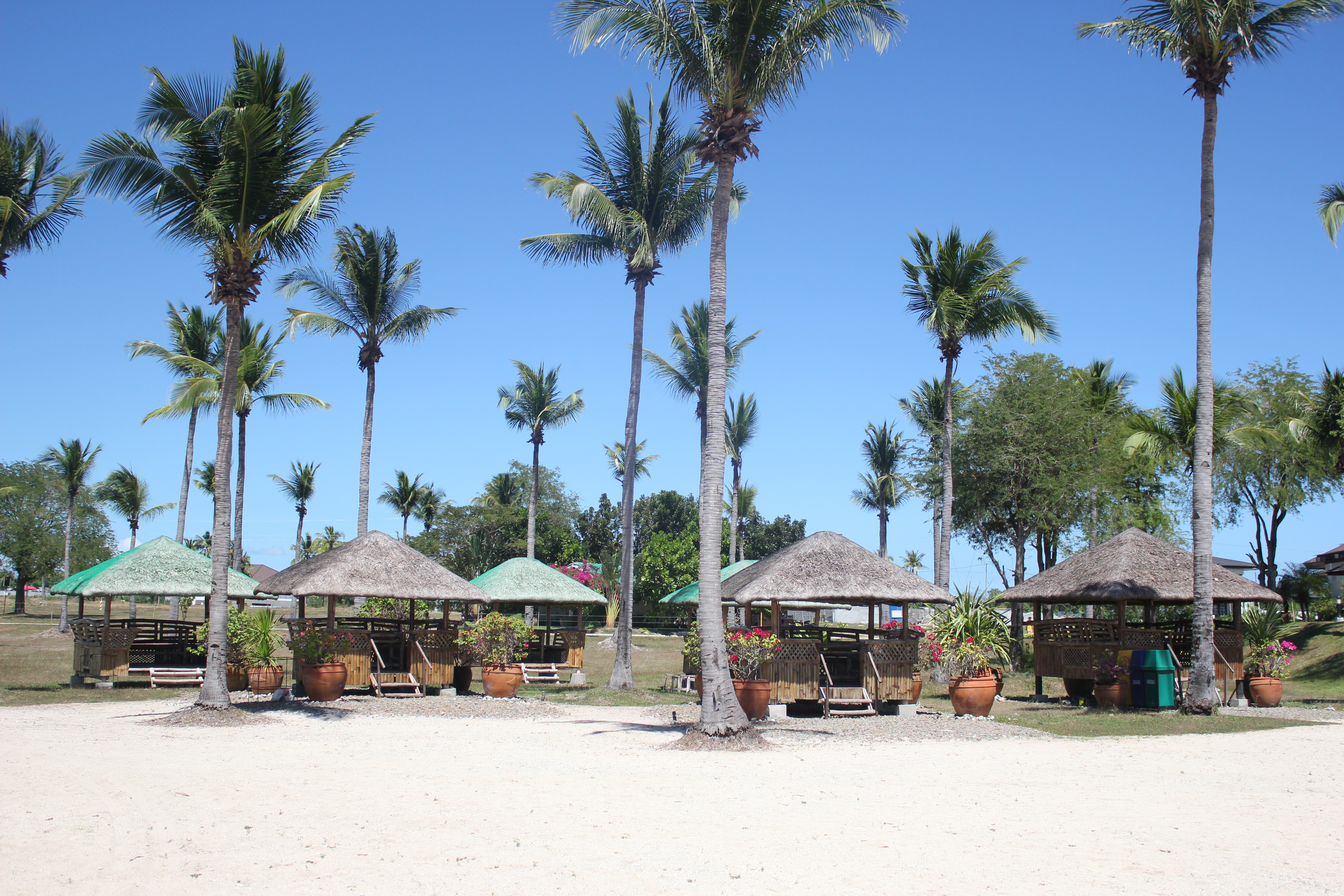 Huts by the beach in Tamarind Cove, Porto Laiya